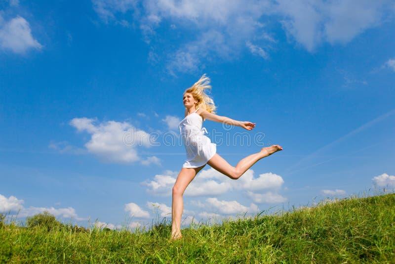 A mulher feliz está funcionando em um campo imagens de stock