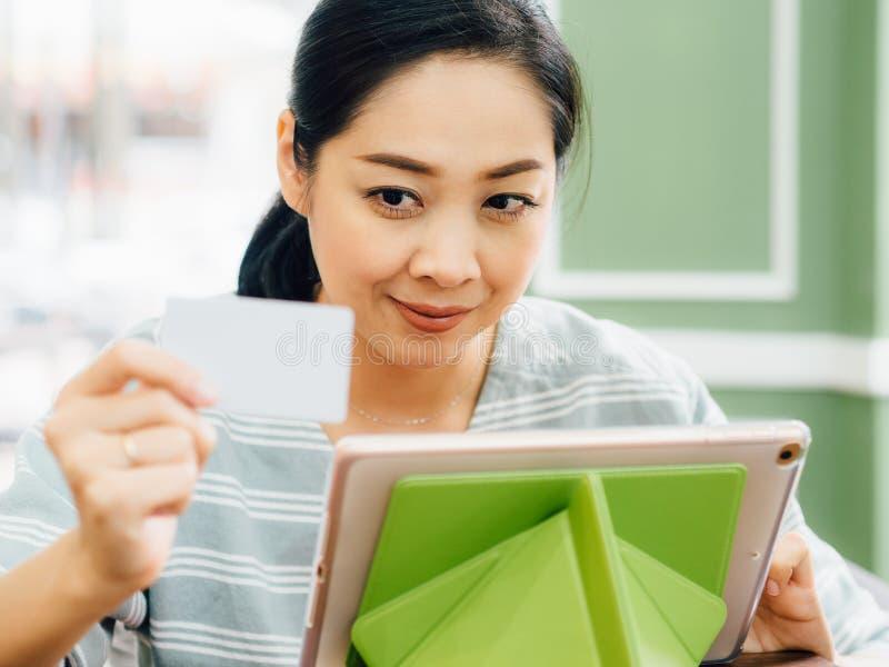 A mulher feliz está usando um cartão de crédito branco do modelo para a compra em linha na tabuleta fotografia de stock royalty free