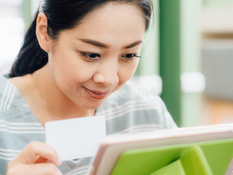 A mulher feliz est? usando um cart?o de cr?dito branco do modelo para a compra em linha na tabuleta foto de stock