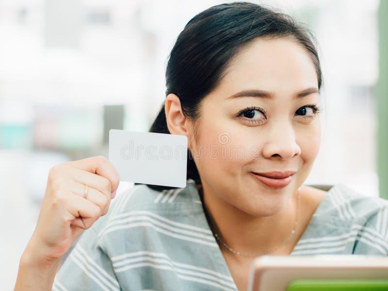 A mulher feliz est? usando um cart?o de cr?dito branco do modelo para a compra em linha na tabuleta fotografia de stock