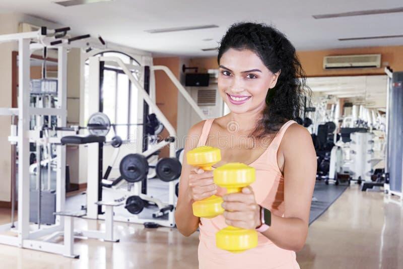 A mulher feliz exercita seu bíceps com pesos fotos de stock