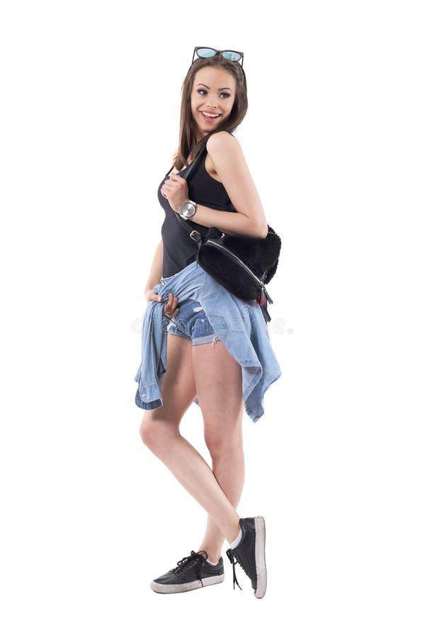 Mulher feliz flirty nova brincalhão lindo na roupa à moda moderna que olha para trás sobre o ombro imagens de stock