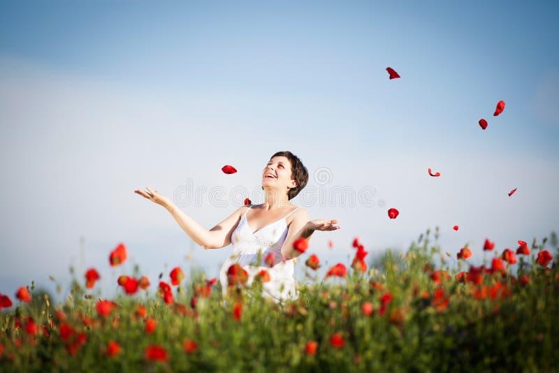 Mulher feliz grávida em um campo de florescência da papoila imagem de stock