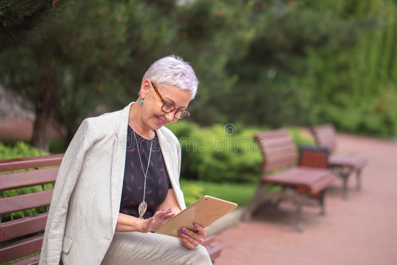 Mulher feliz idosa com a tabuleta no banco imagem de stock royalty free