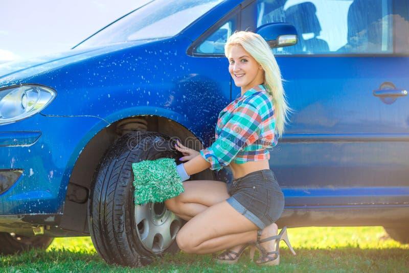 A mulher feliz lava o carro foto de stock