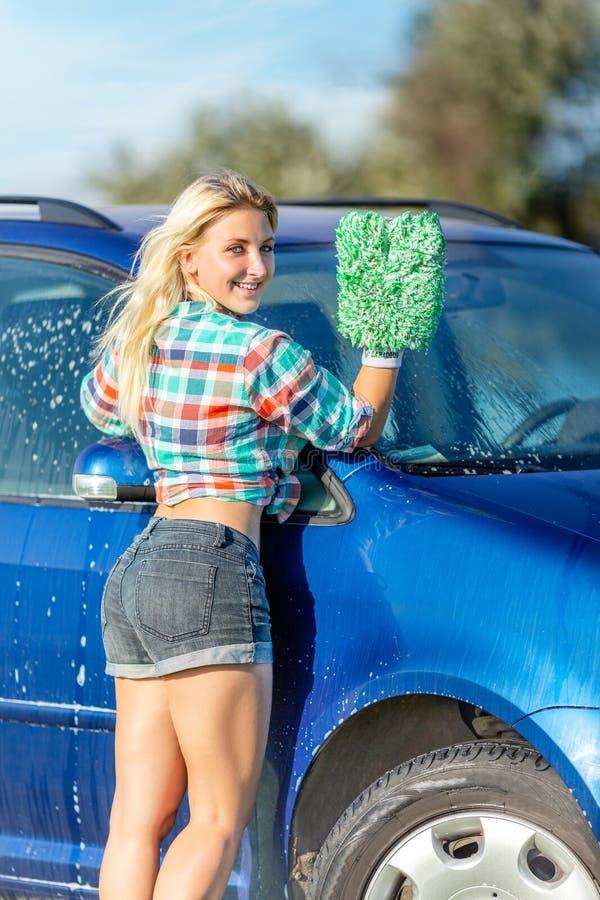 A mulher feliz lava o carro fotografia de stock