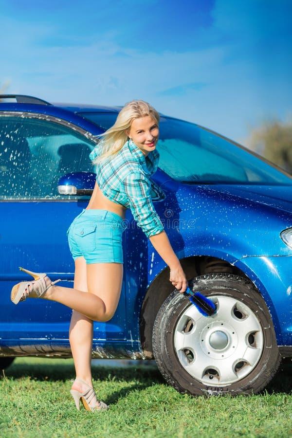 A mulher feliz lava o carro fotos de stock