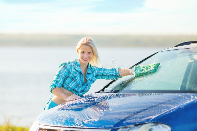 A mulher feliz lava o carro imagens de stock