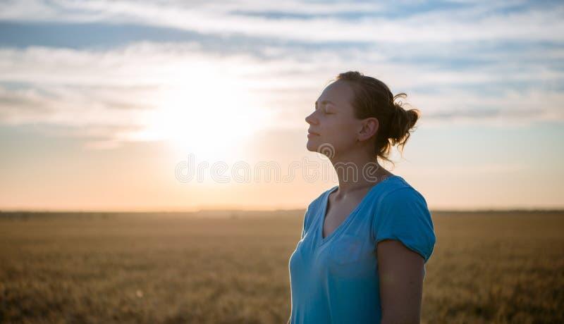 Mulher feliz livre que aprecia a natureza e a liberdade exteriores Mulher com os braços estendido em um campo de trigo no por do  fotografia de stock royalty free