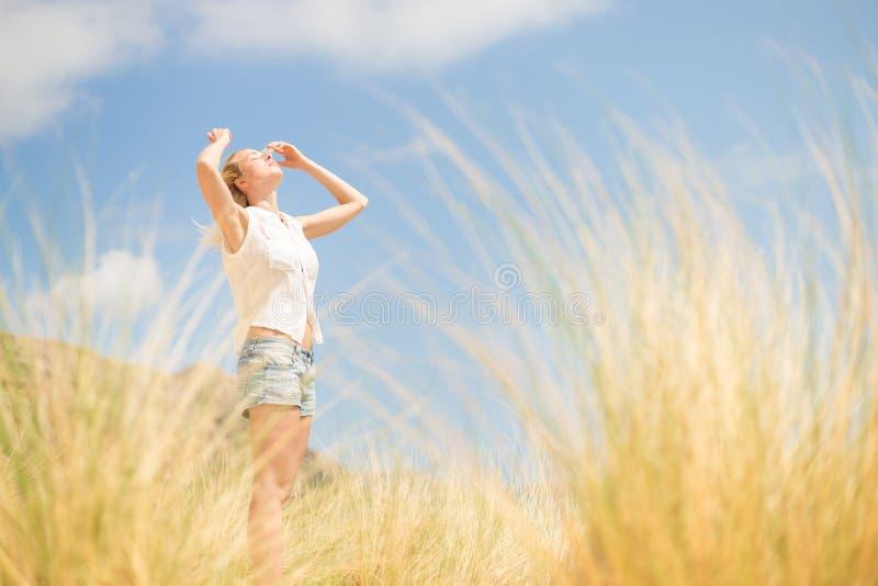 Mulher feliz livre que aprecia Sun em férias imagens de stock royalty free