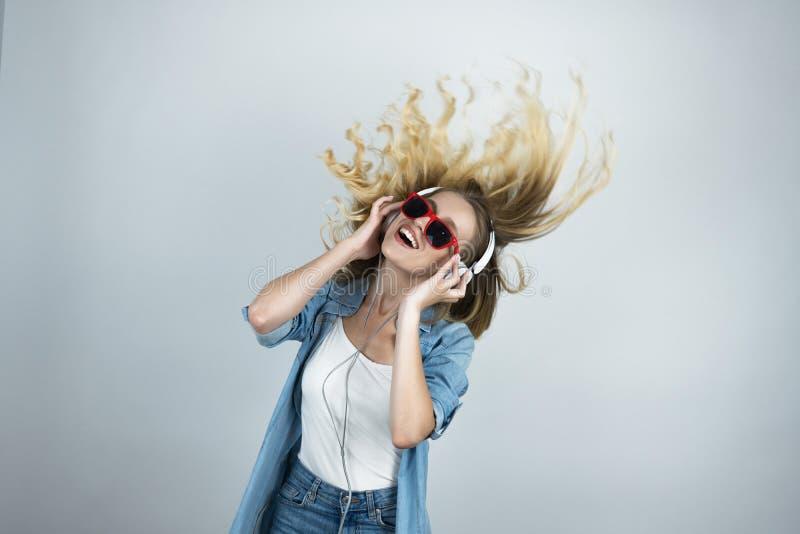 Mulher feliz loura nos fones de ouvido e nos óculos de sol que escuta o fundo isolado branco de dança da música no movimento fotografia de stock royalty free