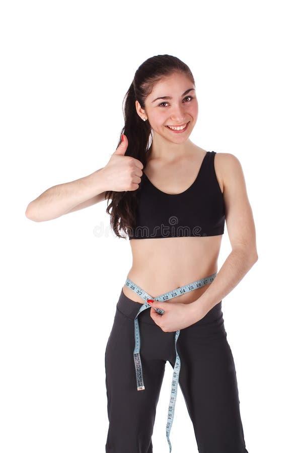 A mulher feliz mede sua cintura imagem de stock
