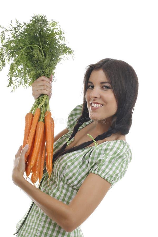 A mulher feliz mostra em um grupo das cenouras fotos de stock