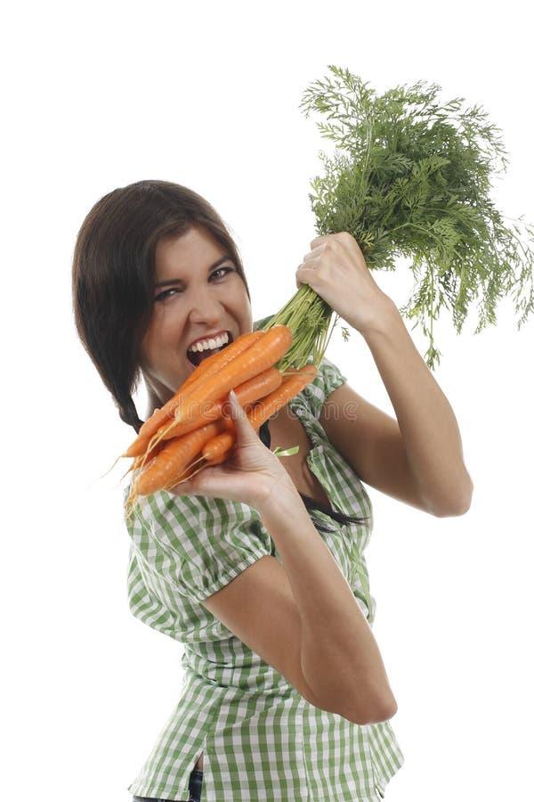 A mulher feliz mostra em um grupo das cenouras foto de stock