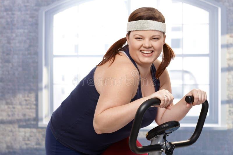 Mulher feliz na bicicleta de exercício fotos de stock