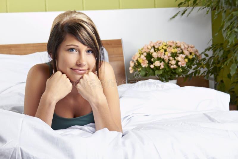 Mulher feliz na cama foto de stock