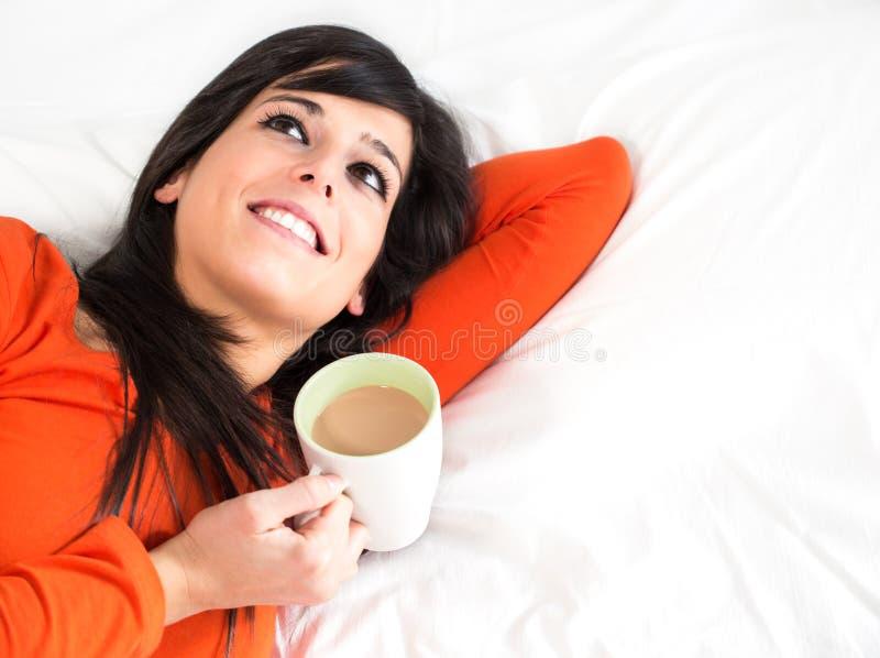 Mulher feliz na cama com chávena de café fotos de stock royalty free