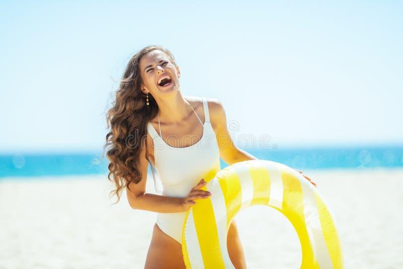 Mulher feliz na costa do oceano que guarda o boia salva-vidas inflável amarelo fotografia de stock