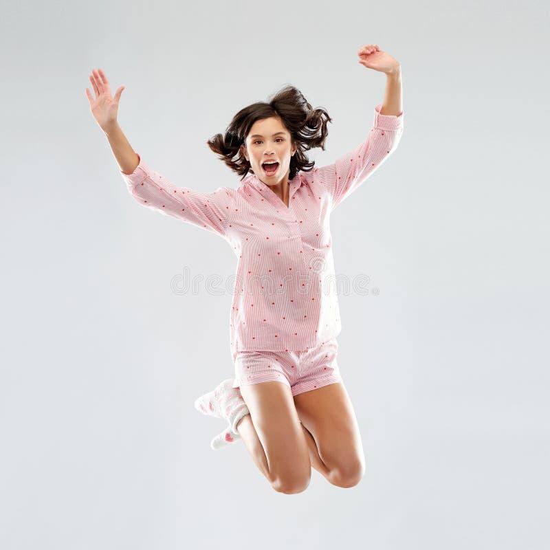 Mulher feliz na eleva??o de salto do pijama fotos de stock