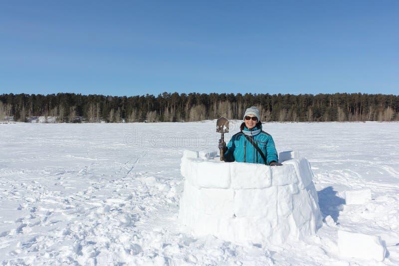 Mulher feliz na roupa morna que constrói um iglu em uma clareira da neve no inverno imagem de stock