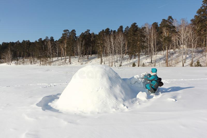 Mulher feliz na roupa morna que constrói um iglu em uma clareira no inverno, Sibéria da neve, Rússia imagens de stock royalty free
