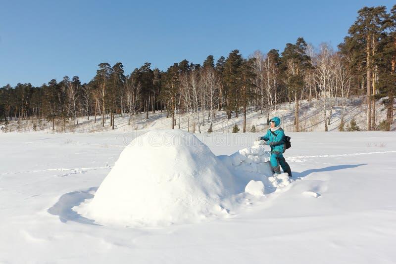 Mulher feliz na roupa morna que constrói um iglu em uma clareira no inverno, Sibéria da neve, Rússia imagem de stock royalty free