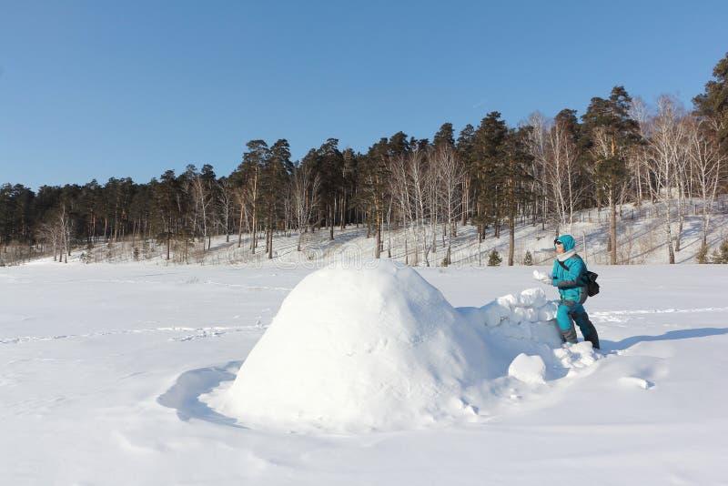 Mulher feliz na roupa morna que constrói um iglu em uma clareira no inverno, Sibéria da neve, Rússia imagem de stock