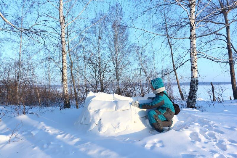 Mulher feliz na roupa morna que constrói um iglu em uma clareira no inverno, Sibéria da neve, Rússia fotografia de stock