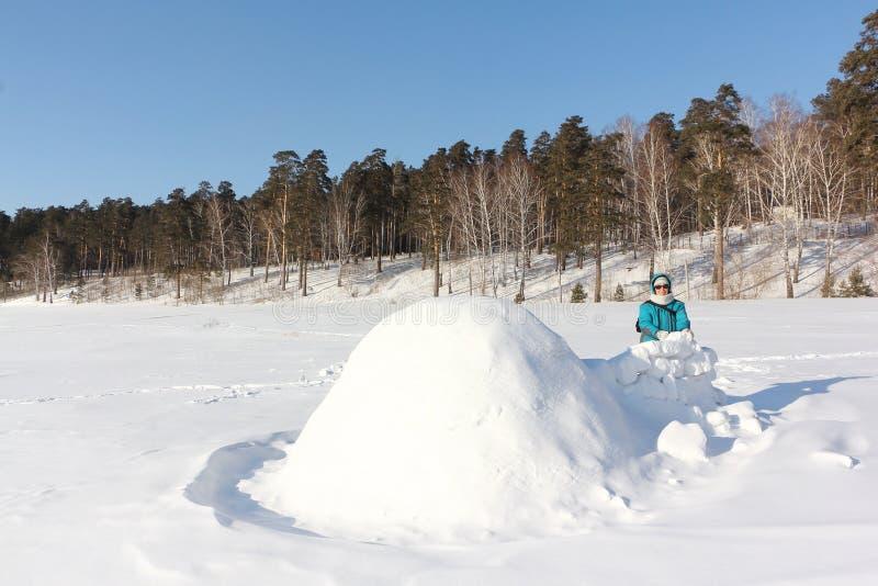Mulher feliz na roupa morna que está perto do iglu em uma clareira no inverno, Sibéria da neve, Rússia fotos de stock royalty free