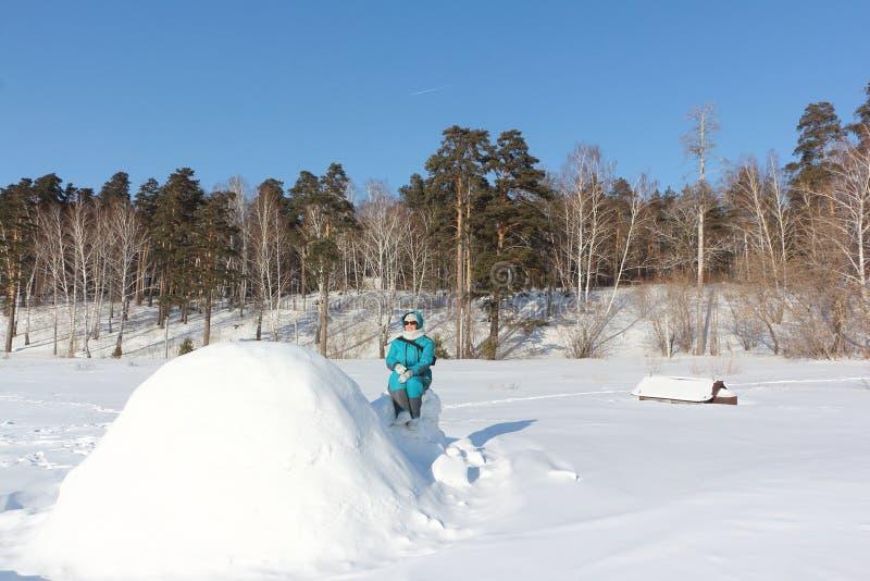 Mulher feliz na roupa morna que senta-se perto de um iglu, Sibéria, Rússia foto de stock royalty free