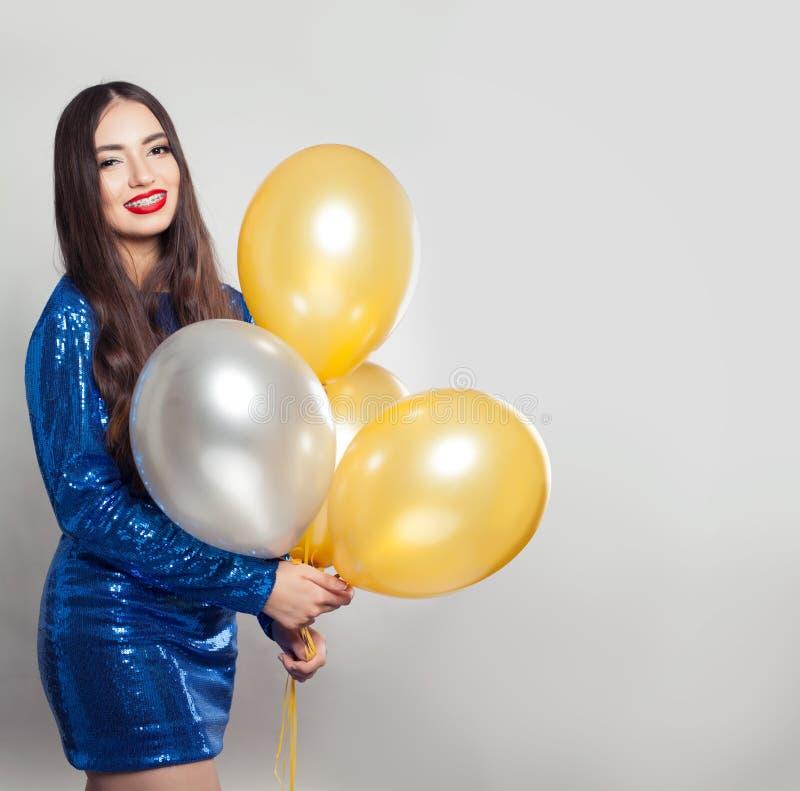A mulher feliz nas lantejoulas veste-se com os balões no fundo branco fotografia de stock royalty free
