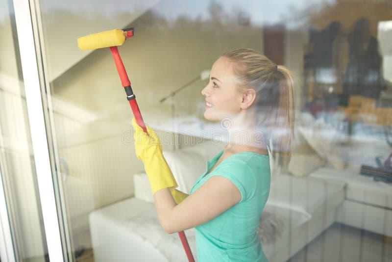 Mulher feliz nas luvas que limpam a janela com a esponja fotografia de stock royalty free