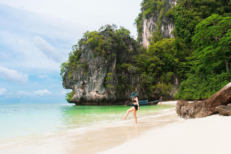 Mulher feliz no biquini e sunhat que andam na praia do mar fotos de stock