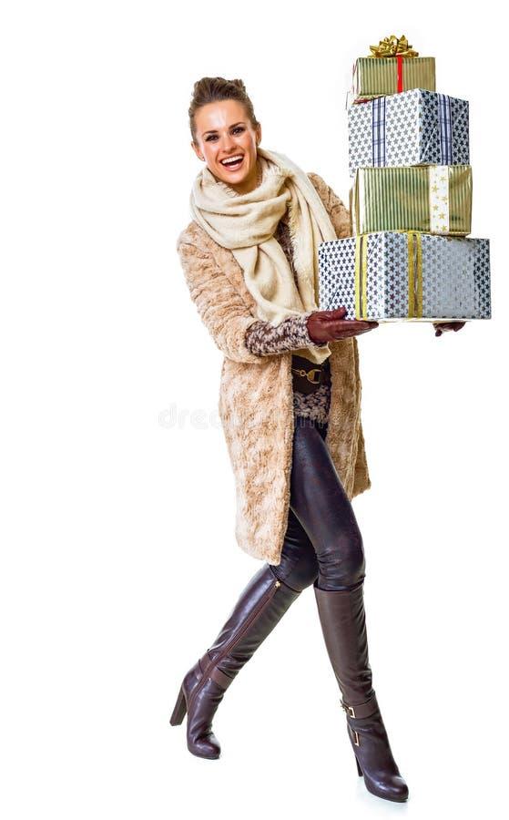 Mulher feliz no branco com a pilha do passeio dos giftes do Natal foto de stock