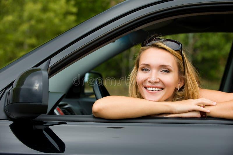 Mulher feliz no carro novo foto de stock