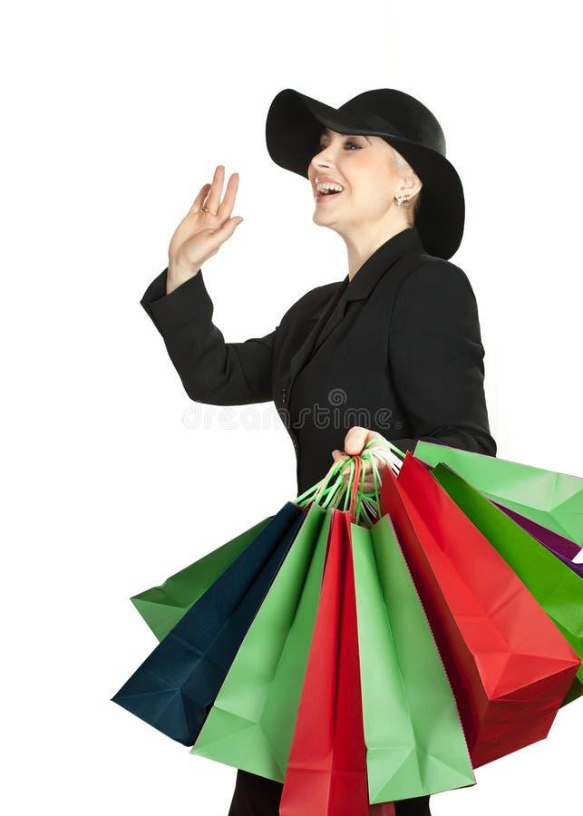 Mulher feliz no chapéu com os sacos de papel no fundo branco fotos de stock royalty free