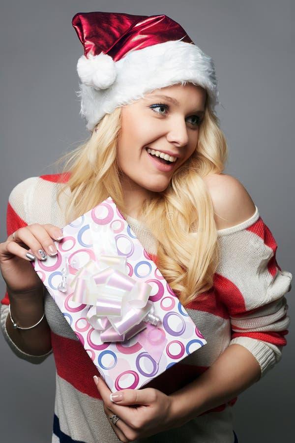 Mulher feliz no chapéu de Santa Claus com caixa de presente imagem de stock royalty free