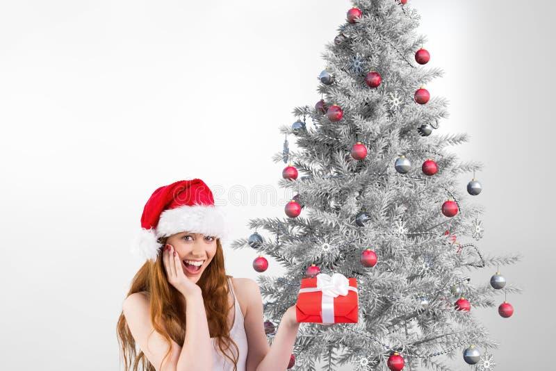 Mulher feliz no chapéu de Santa que mantém um presente contra o fundo do Natal imagens de stock royalty free