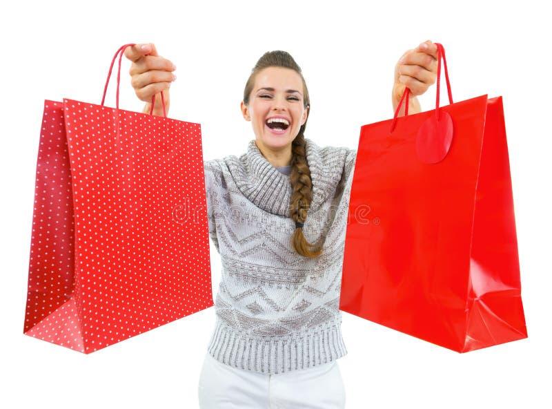Mulher feliz no chapéu do Natal que mostra sacos de compras do Natal imagem de stock