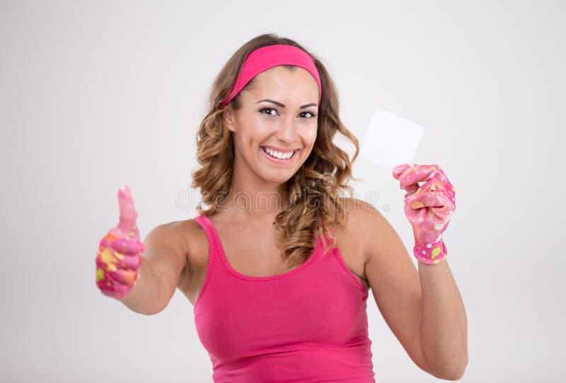 Mulher feliz no equipamento da limpeza que guarda um pedaço de papel foto de stock royalty free