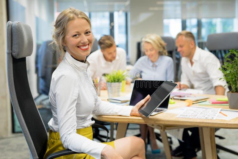 Mulher feliz no escritório que trabalha no grupo foto de stock