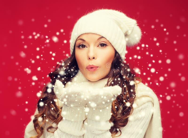 A mulher feliz no inverno veste o sopro nas palmas imagens de stock