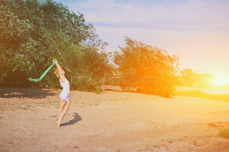 Mulher feliz no pôr do sol na natureza no verão com mãos abertas Jovem relaxando no verão, no céu ao ar livre, ao ar livre foto de stock royalty free