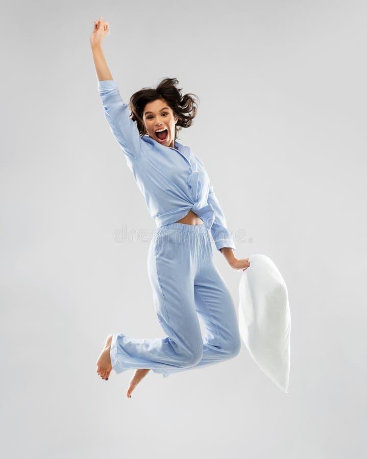Mulher feliz no pijama azul que salta com descanso foto de stock royalty free