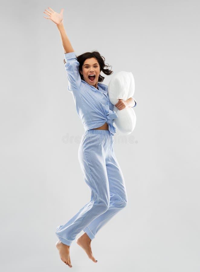 Mulher feliz no pijama azul que salta com descanso fotos de stock