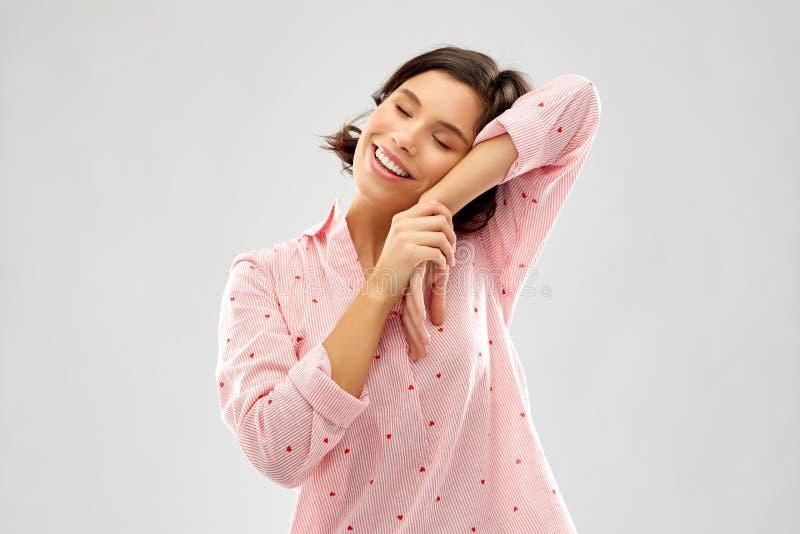 Mulher feliz no pijama que faz o gesto do sono fotografia de stock royalty free