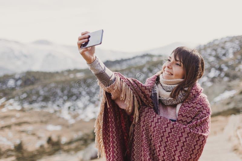 Mulher feliz no por do sol na natureza no outono usando o telefone celular Divertimento fora imagem de stock royalty free