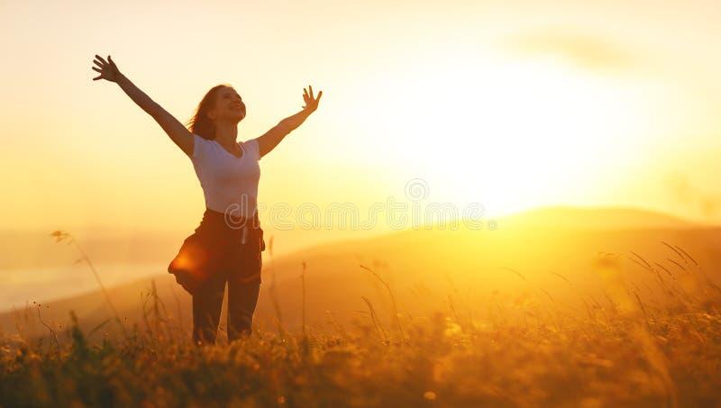 Mulher feliz no por do sol nas mãos abertas do iwith da natureza fotos de stock