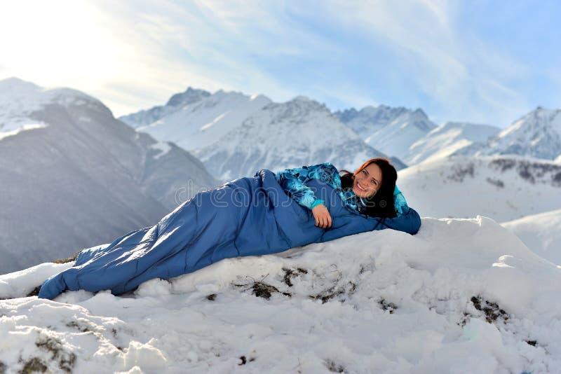 Mulher feliz no saco-cama em montanhas nevados fotos de stock royalty free