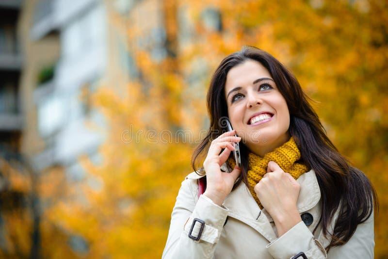 Mulher feliz no telefone celular exterior no outono fotografia de stock royalty free